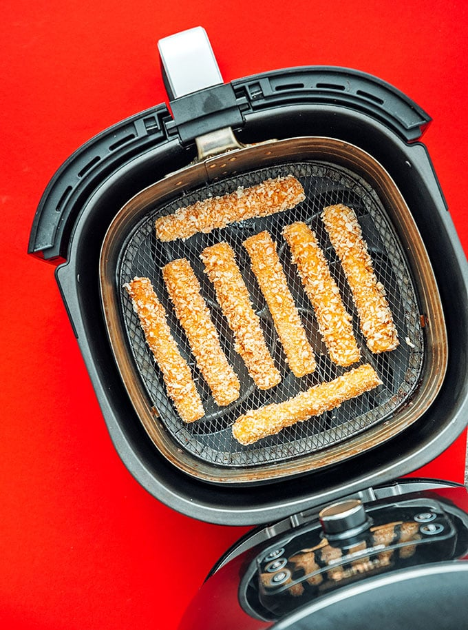 Mozzarella sticks cooking in a single layer in an air fryer