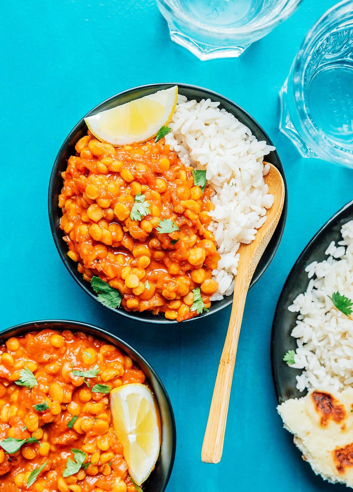 Three bowls of chana dal and rice on a blue background