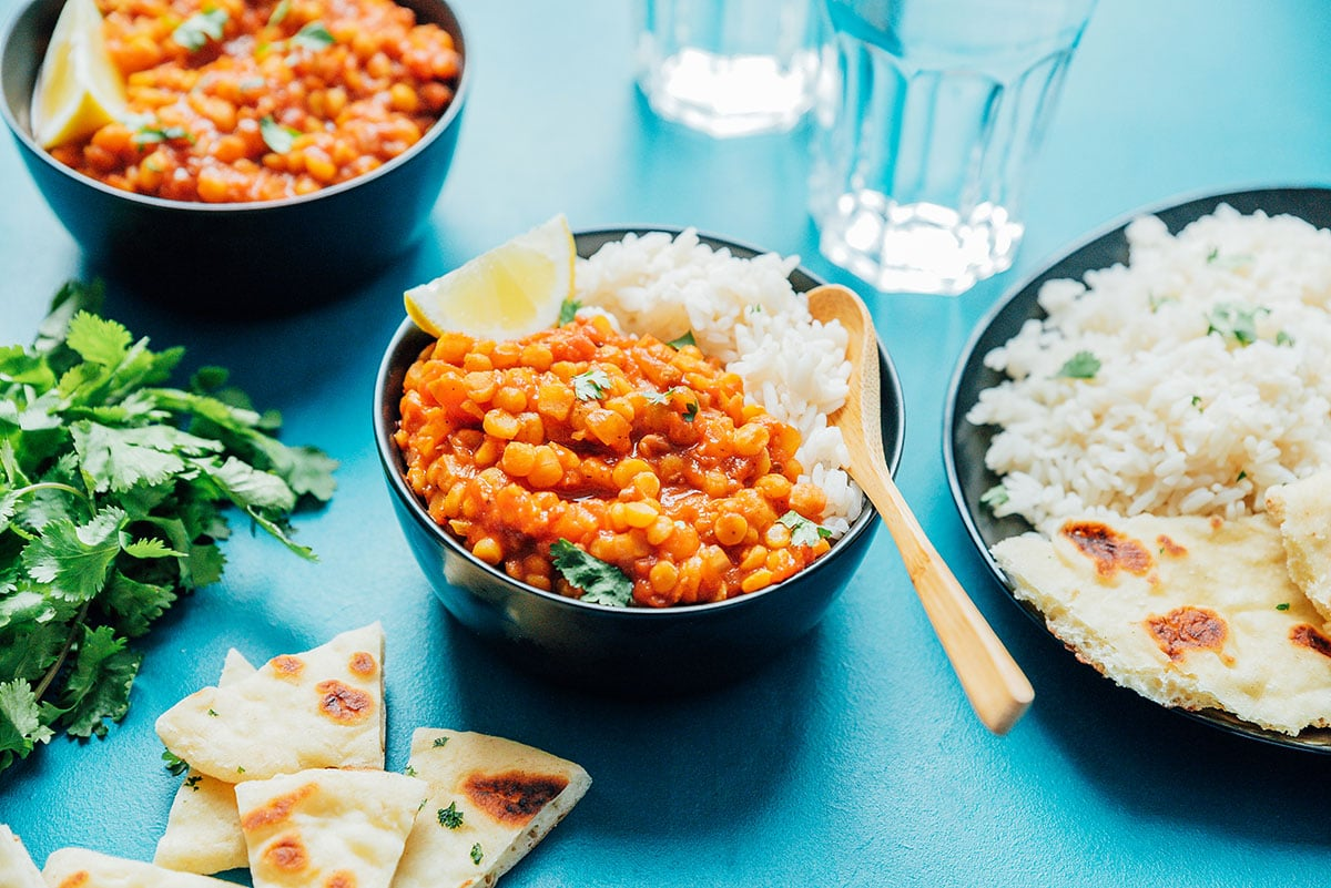 2 bowls of chana dal, naan bread, rice, and cilantro on a blue background