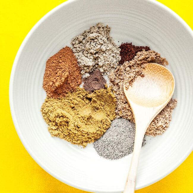 Ingredients to make garama masala on a yellow background