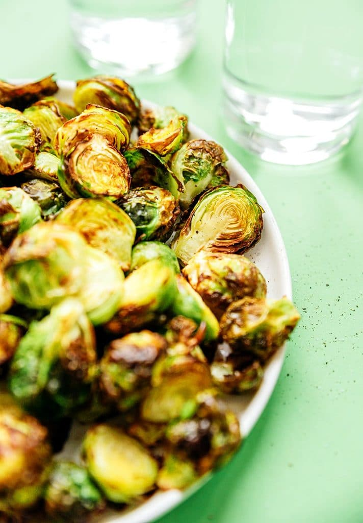 Air fried brussels sprouts in a bowl with green background