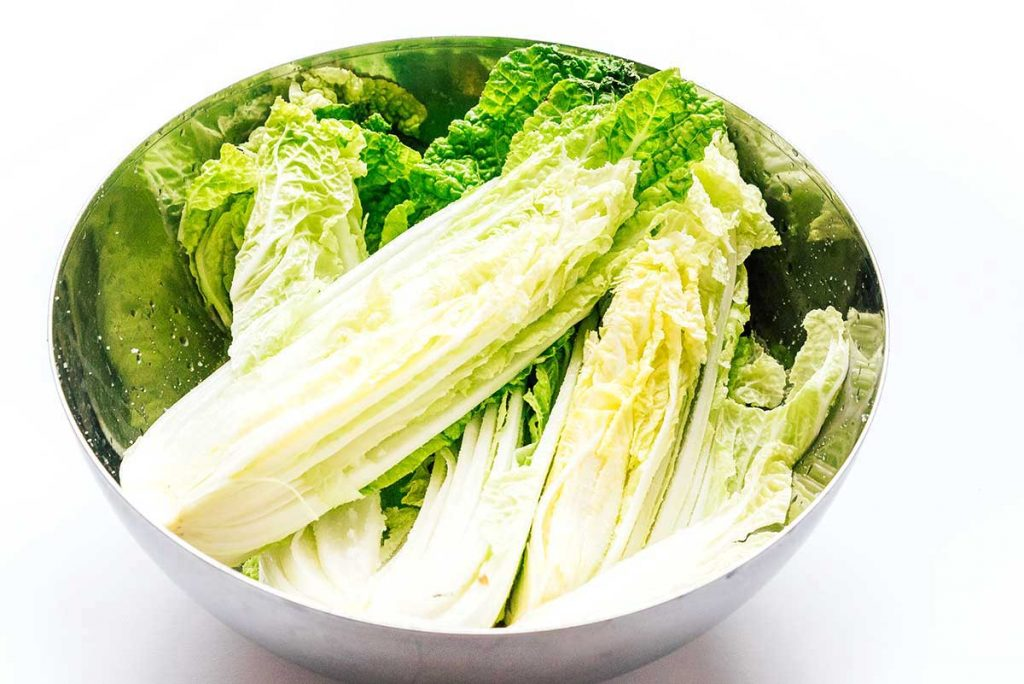 Fresh cabbage in a bowl on a white background