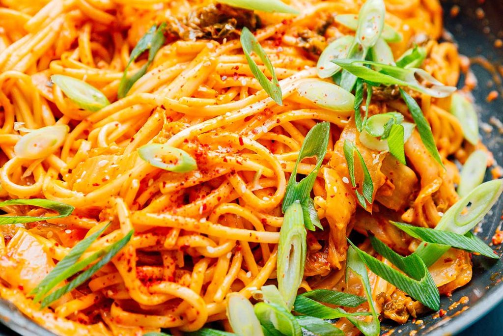 Up close image of kimchi udon noodles topped with green onions