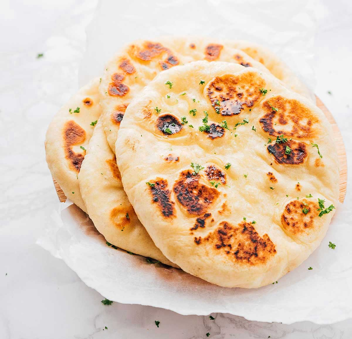 Naan bread slices stacked neatly on a white background