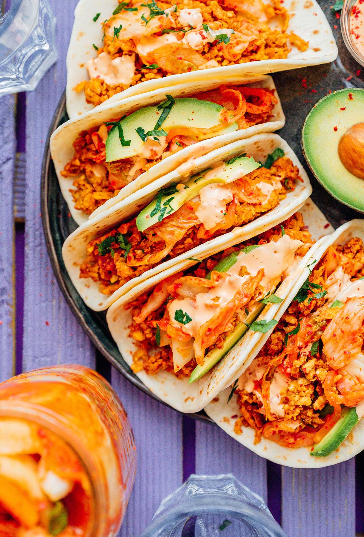 Five kimchi tempeh tacos and half of an avocado on a black plate on a purple table
