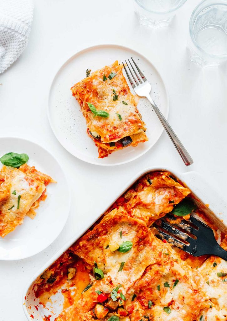 Two plates and a casserole dish of vegetarian lasagna on a white background