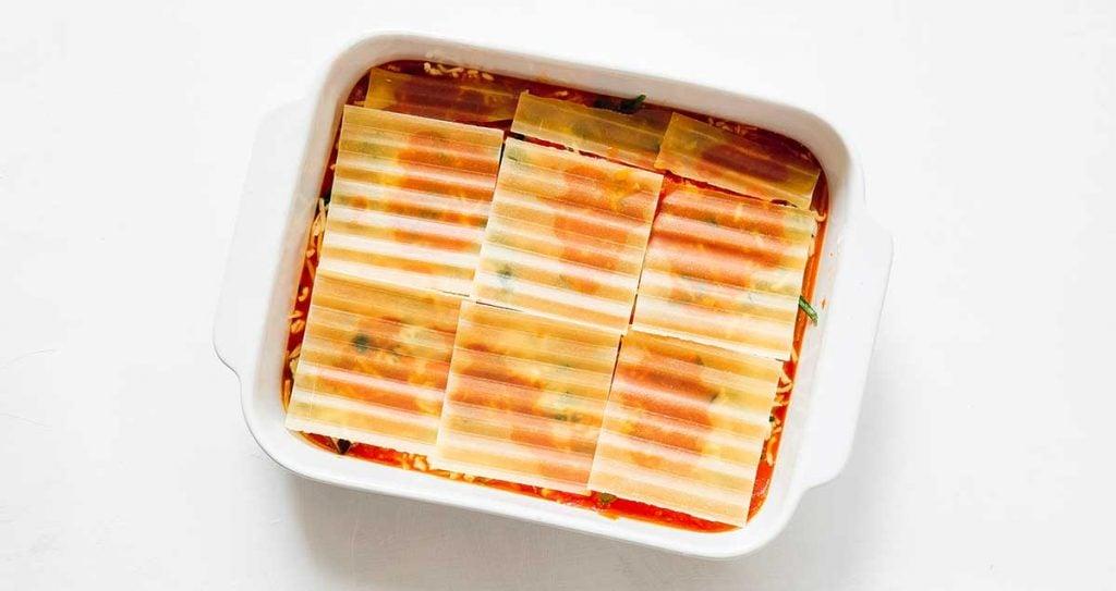 A casserole dish filled with marinara, mozzarella, and lasagna noodles