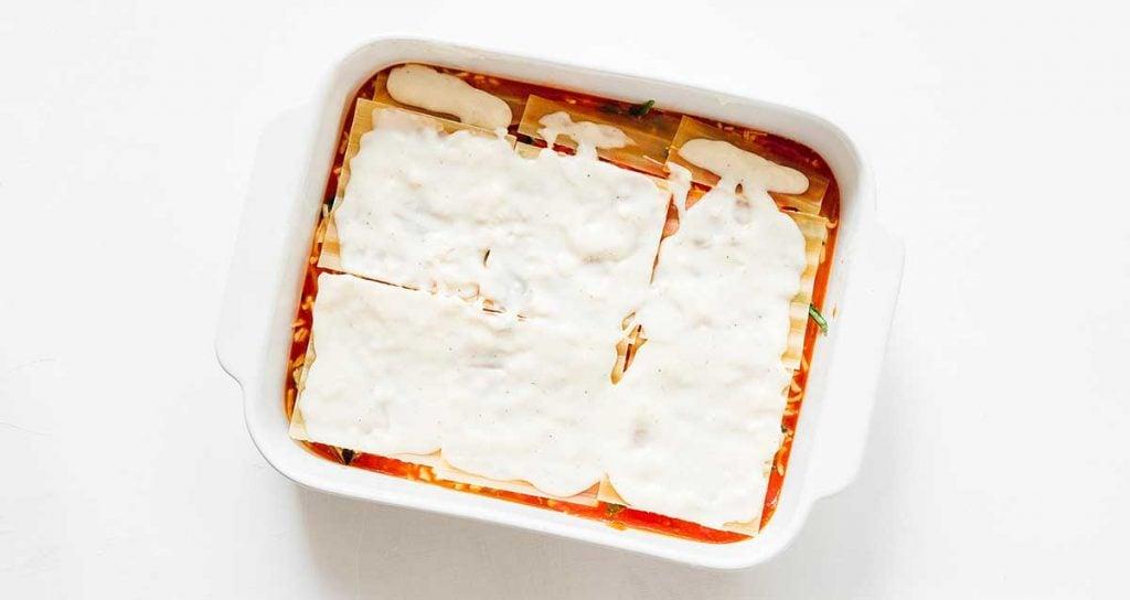 A casserole dish filled with marinara, mozzarella, lasagna noodles, and bechamel