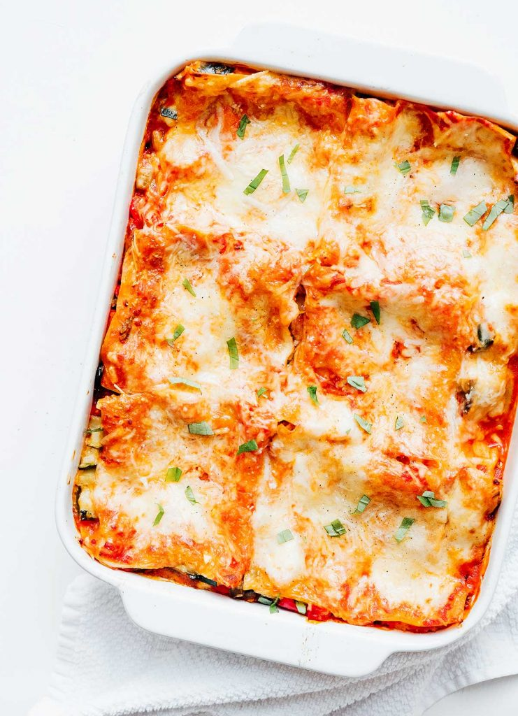 Baked vegetarian lasagna in a casserole dish on a white background