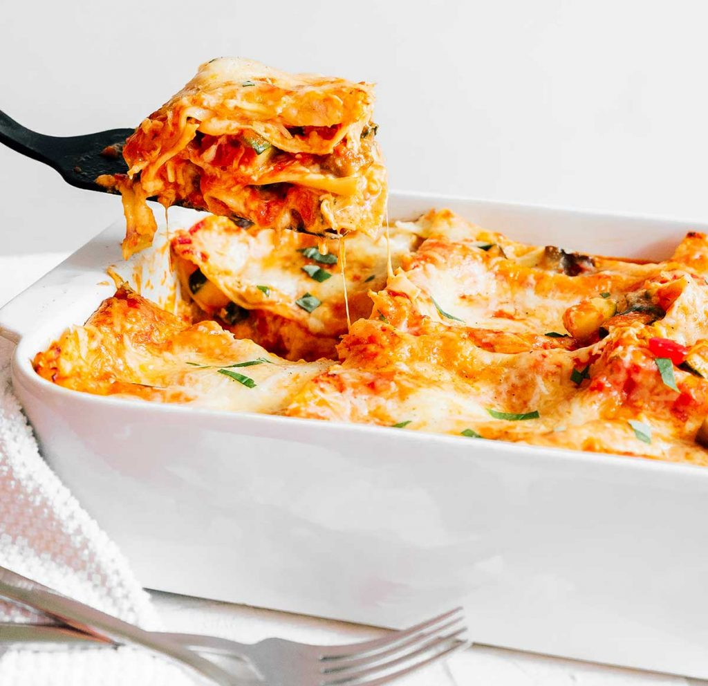 A black spatula scooping a serving of vegetarian lasagna from the casserole dish