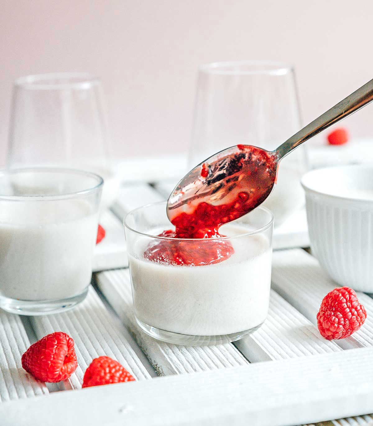Dropping a spoonful of raspberry topping onto a serving of panna cotta in a cup