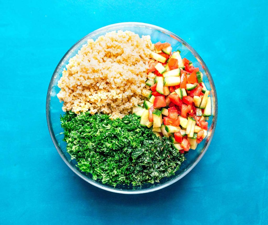 Glass bowl filled with bulgur, tomato, cucumber, parsley, and mint