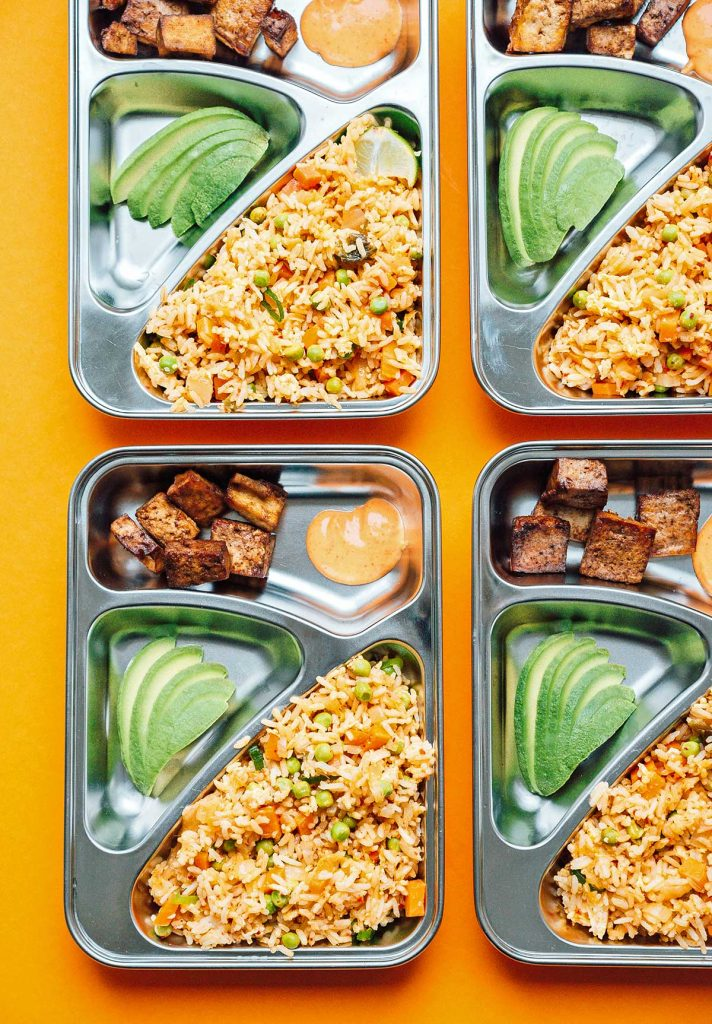 Four meal prep containers filled with kimchi fried rice, tofu, and avocado slices on a yellow background