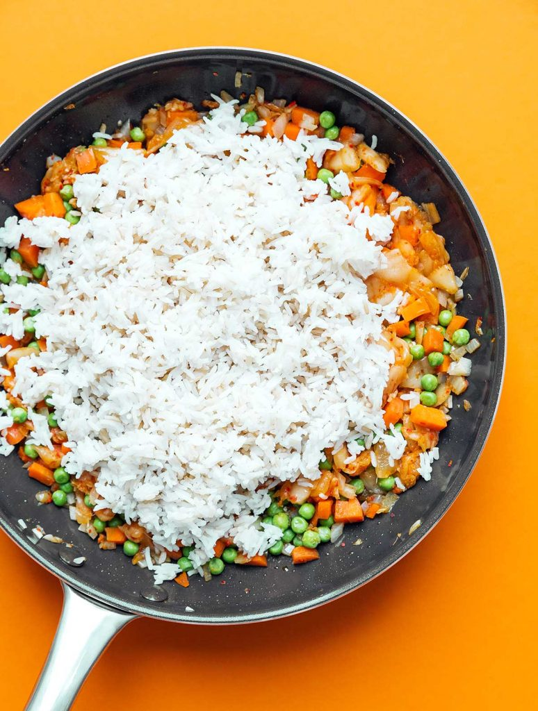 Vegetables, kimchi, and rice cooking in a skillet on an orange background