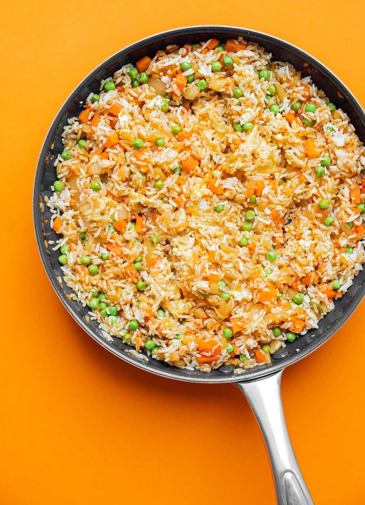 Kimchi fried rice cooking in a skillet on an orange background