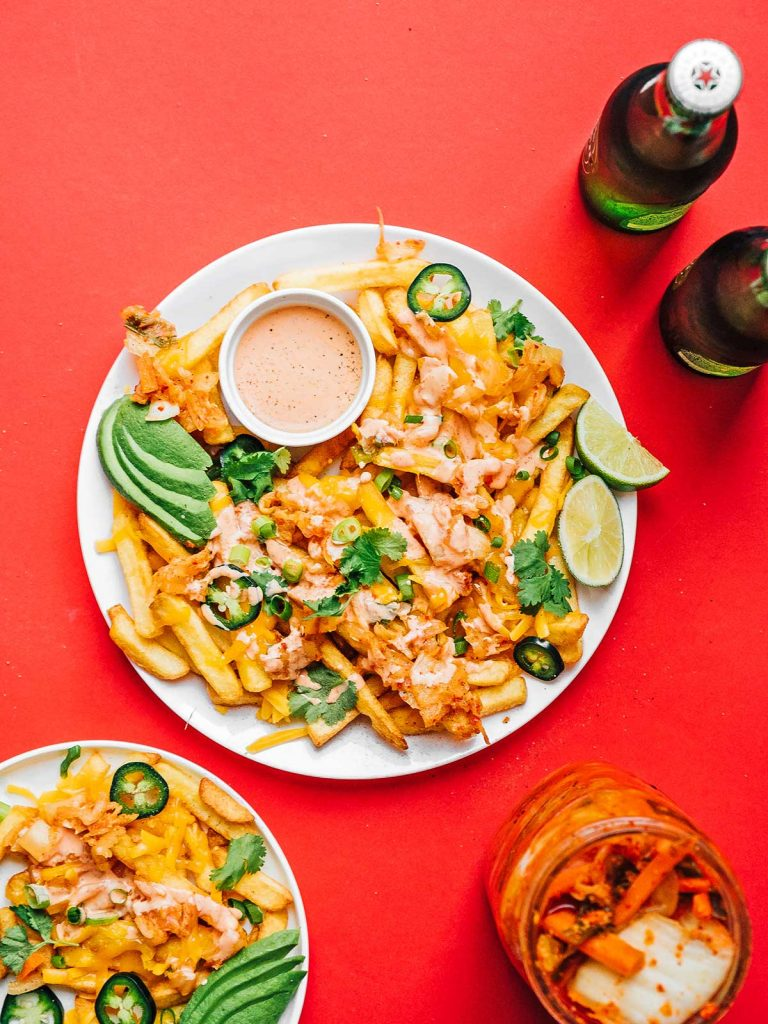 Bird's eye photo of kimchi fries, sauce, avocado slices, lime slices, and toppings on a plate on a red background