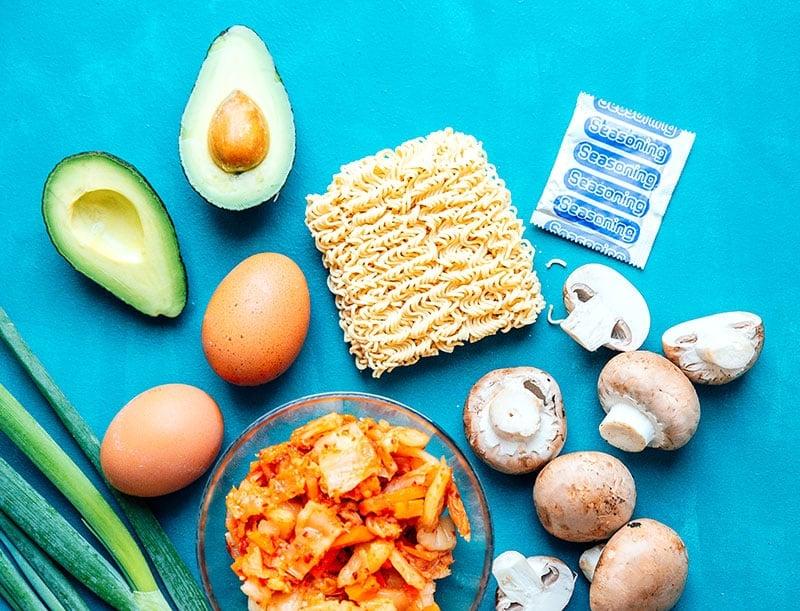 Bird's eye view of kimchi ramen hack ingredients arranged on a blue background