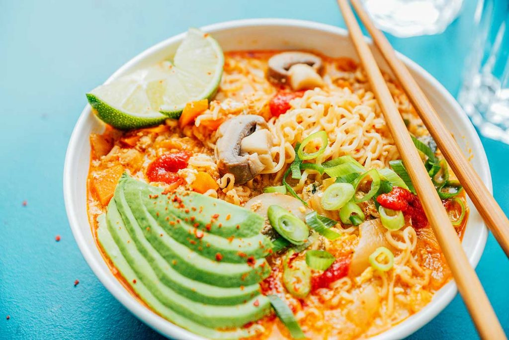 Bowl of kimchi ramen loaded with toppings on a blue background