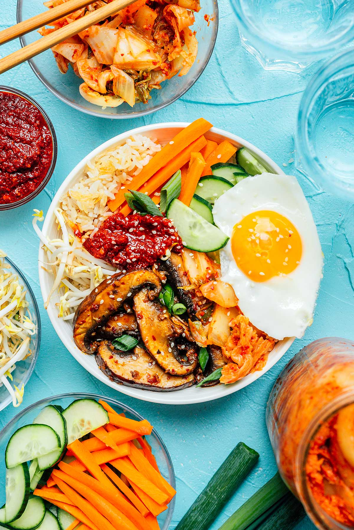 Bowl of kimchi bibimbap surrounded by various toppings on a blue background
