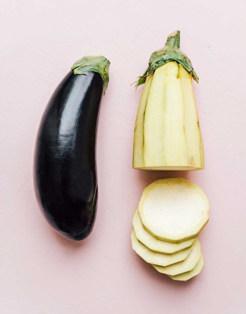 One full eggplant lying beside one peeled, sliced eggplant