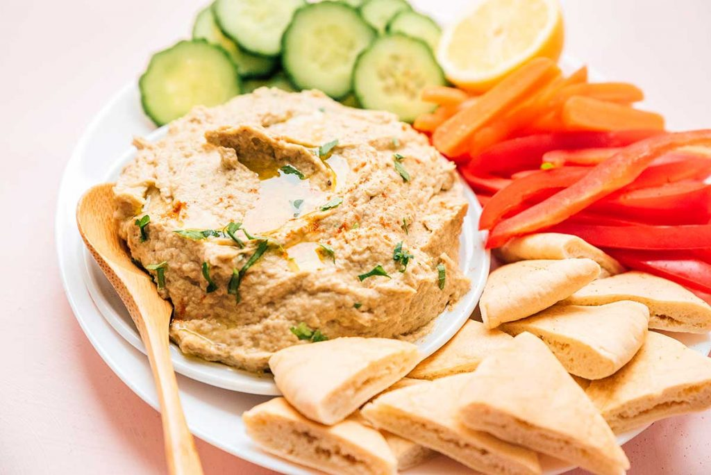 Detailed close up of baba ganoush on a plate with cucumber slices, carrots, peppers, pita bread, and a lemon wedge.