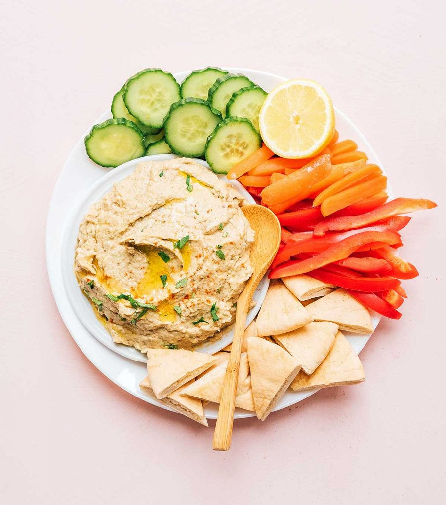 Baba ganoush on a plate with cucumber slices, carrots, peppers, pita bread, and a lemon wedge.