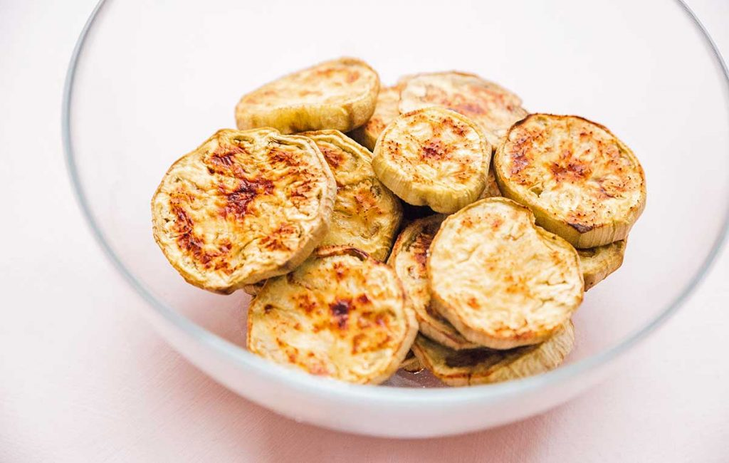 Roasted eggplant slices in a clear bowl