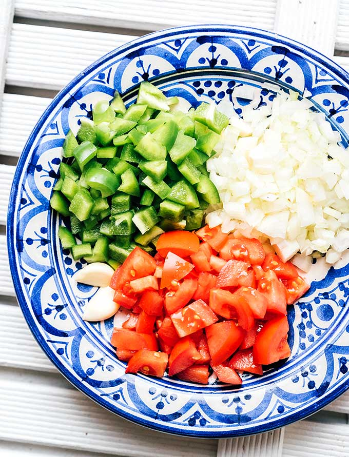 Chopped green bell pepper, white onion, roma tomato, and garlic on a plate.