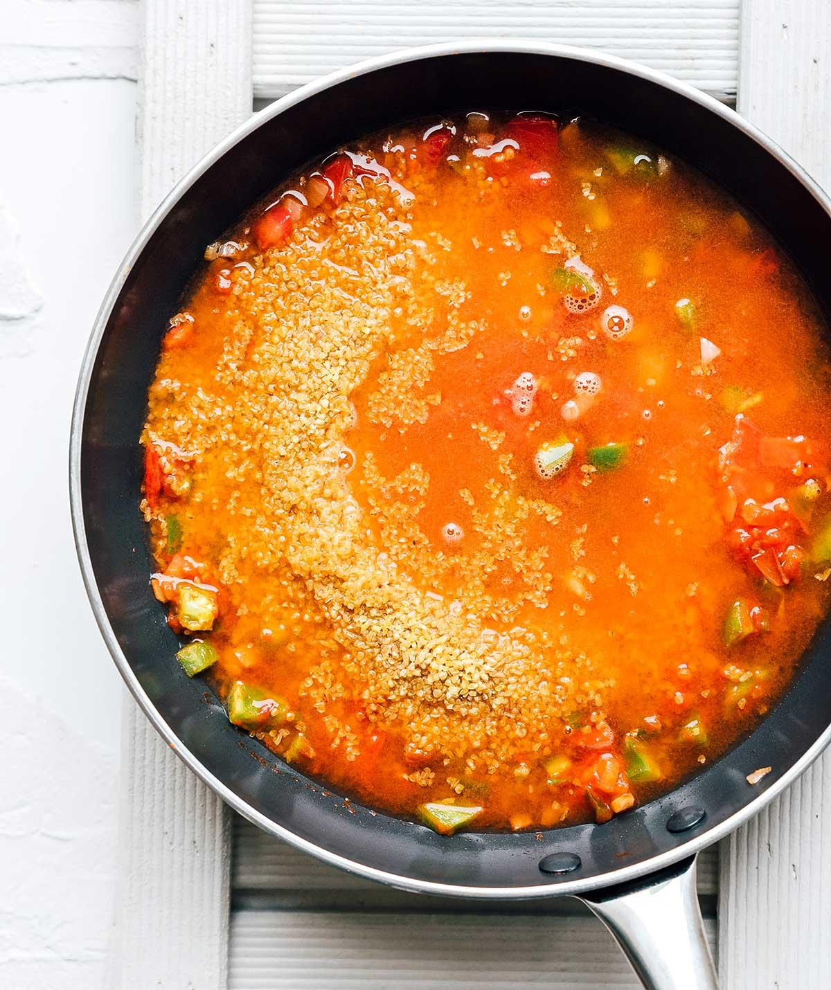 Pan of chopped veggies, diced tomatoes, bulgur, and water.