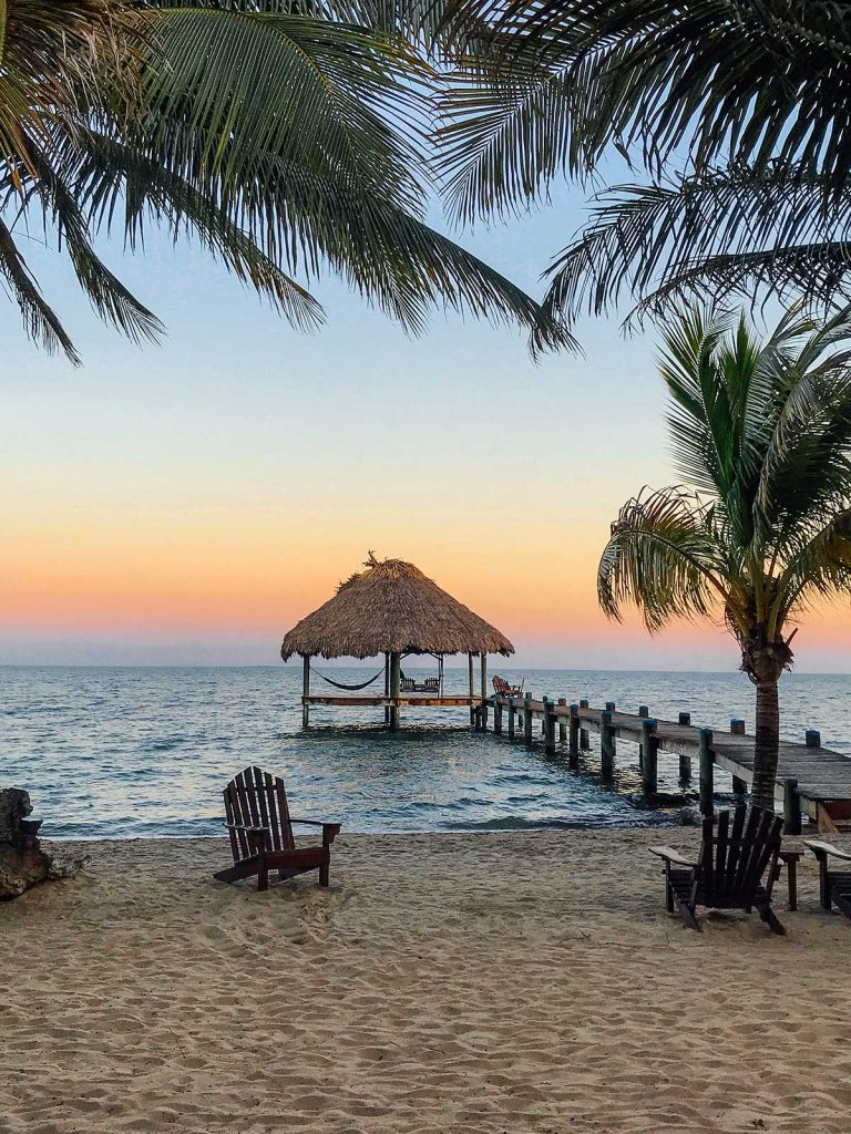 Hut with dock and setting sun over ocean in Belize