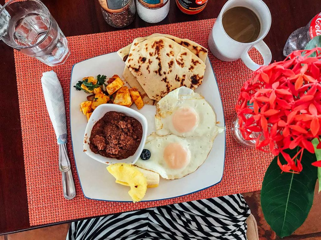 Belizean breakfast with eggs, tortillas, and refried beans