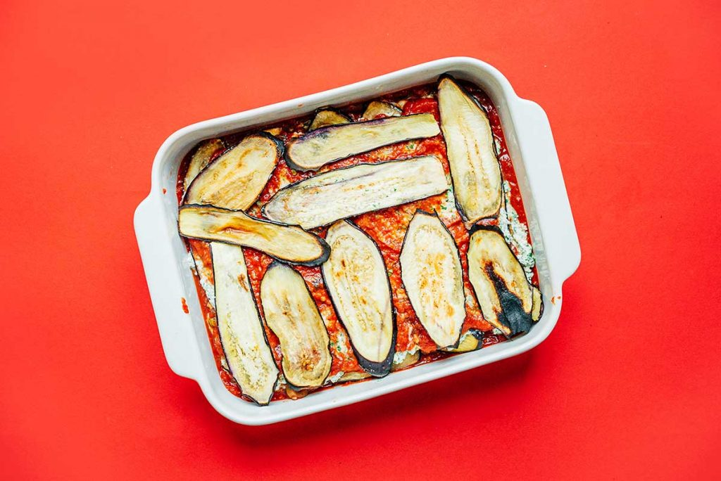 A casserole dish filled with sauce, eggplant, and ricotta layers