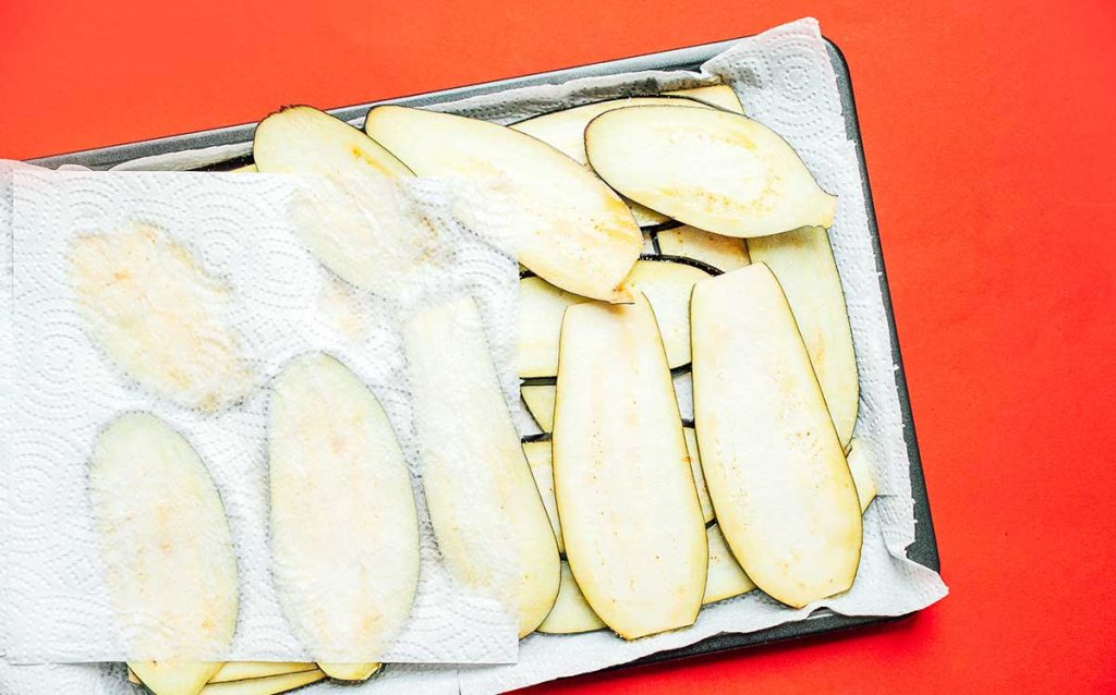 Gently patting salted eggplant slices with a paper towel to remove moisture