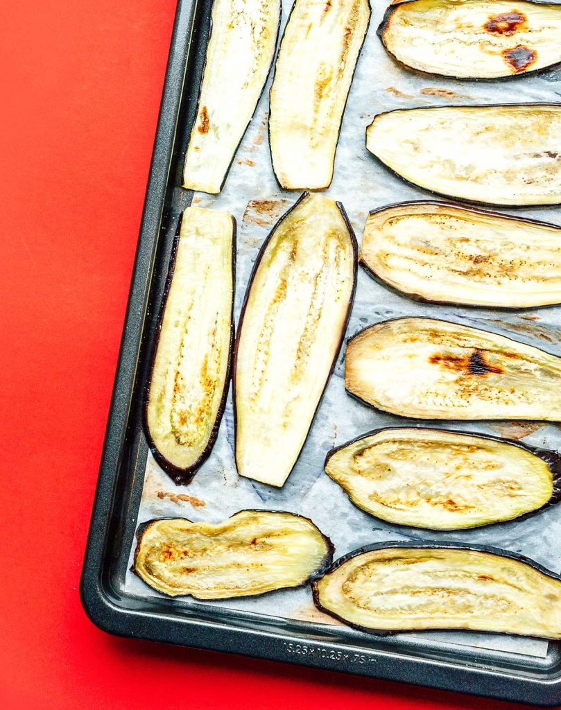 Slightly browned eggplant slices lined up in a single layer on a baking sheet