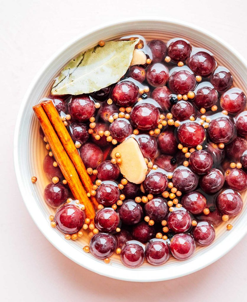 A white bowl filled with the water and vinegar mixture, red seedless grapes, and various spices