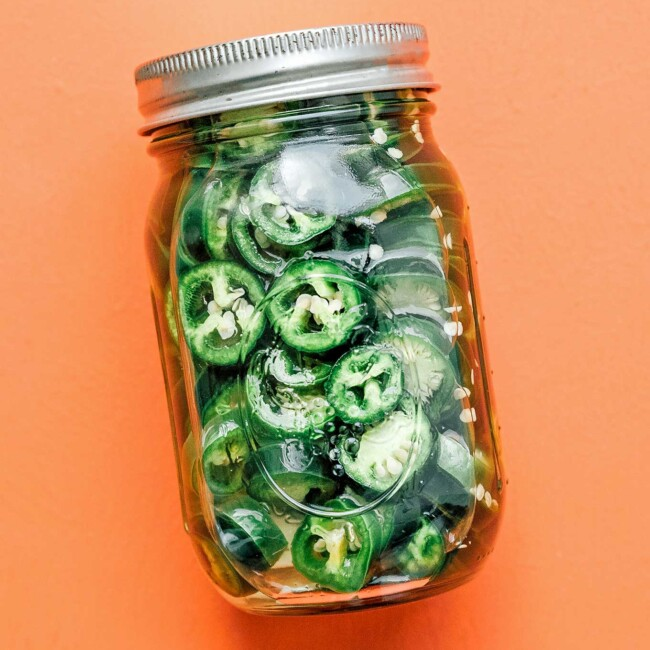 Pickles jalapenos in a jar on an orange background