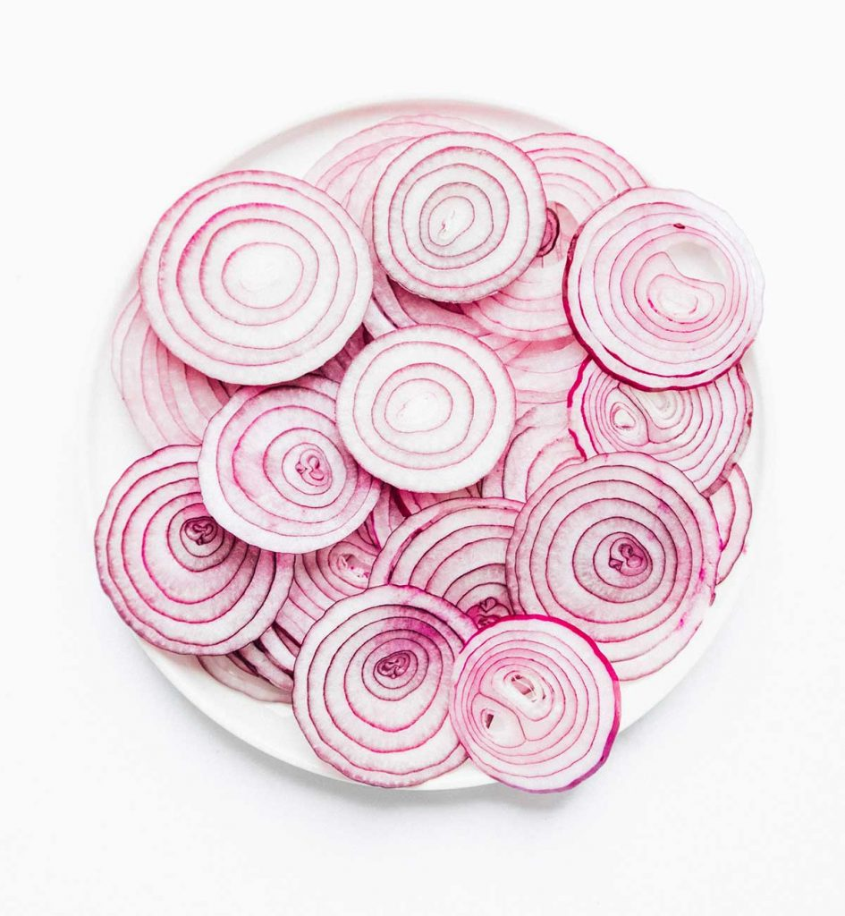 A white plate filled with slices of red onions