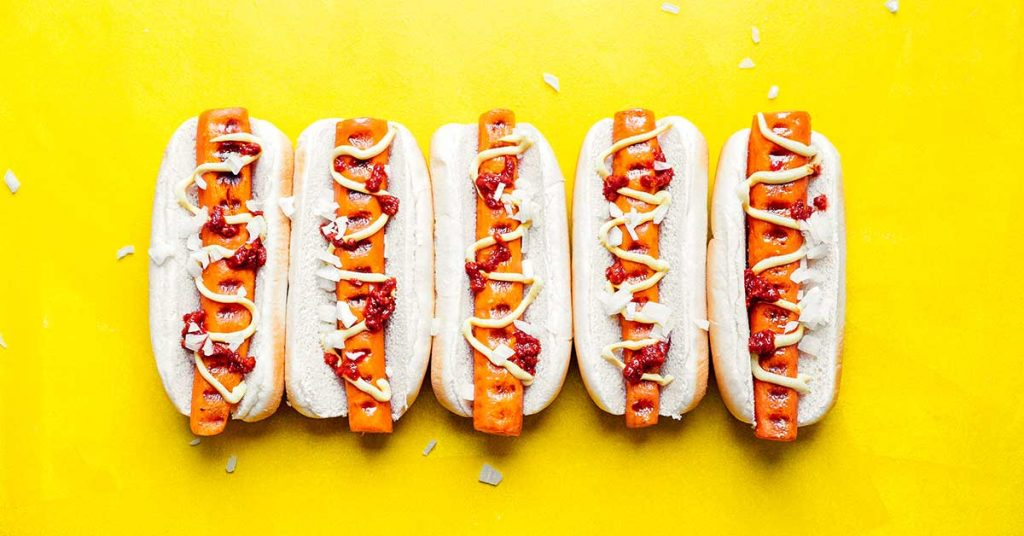 Five vegan hot dogs in buns topped with chopped white onion, ketchup, and mustard