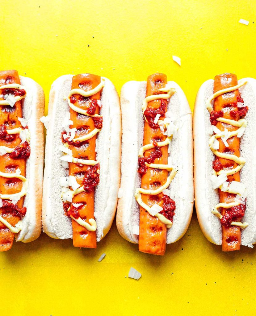 Four carrot hot dogs in buns topped with chopped white onion, ketchup, and mustard