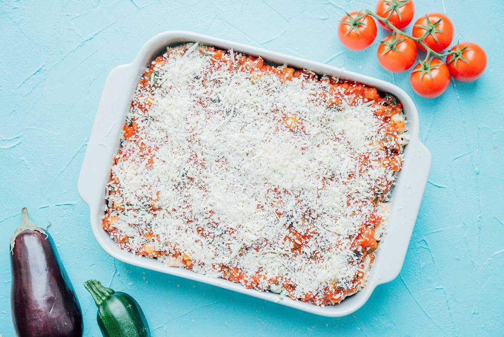 A baking dish filled with sauce, pasta, ricotta, and cheese