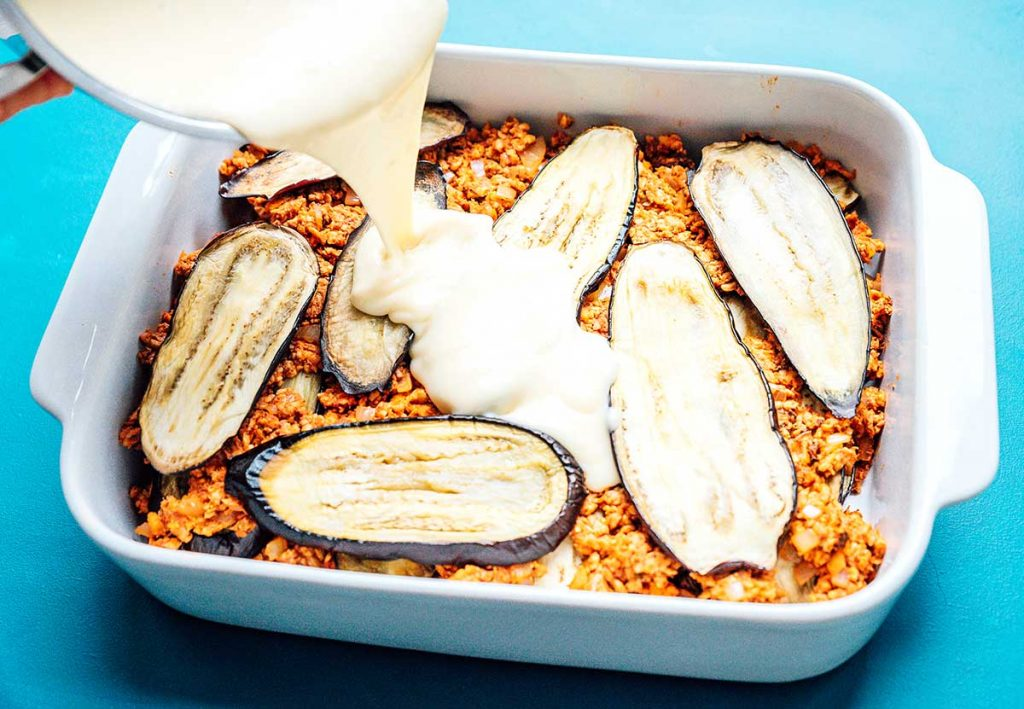 Pouring bechamel into a casserole dish filled with layers of tempeh and eggplant