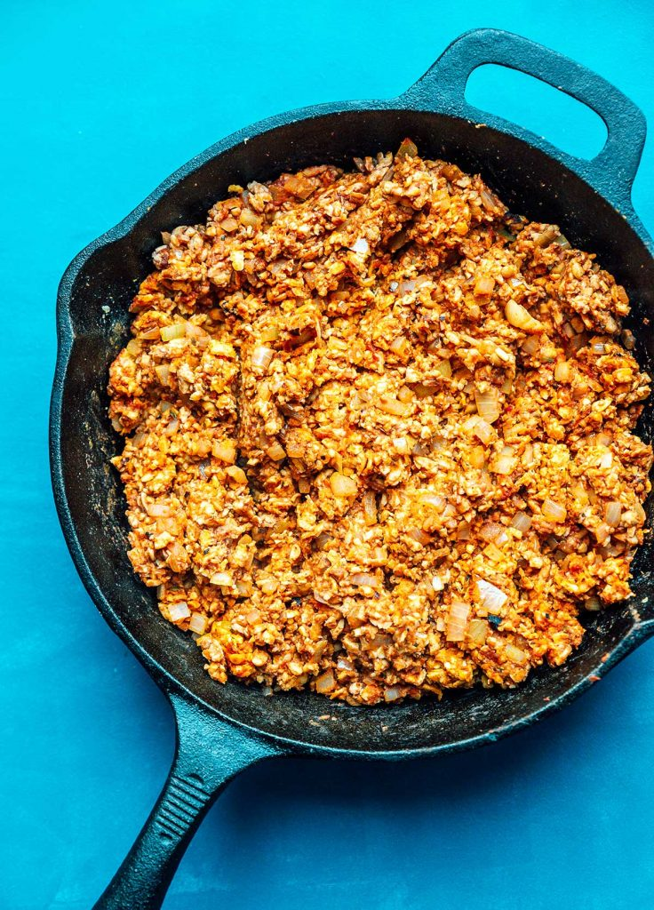 Ground tempeh cooked in a skillet with onion and various spices