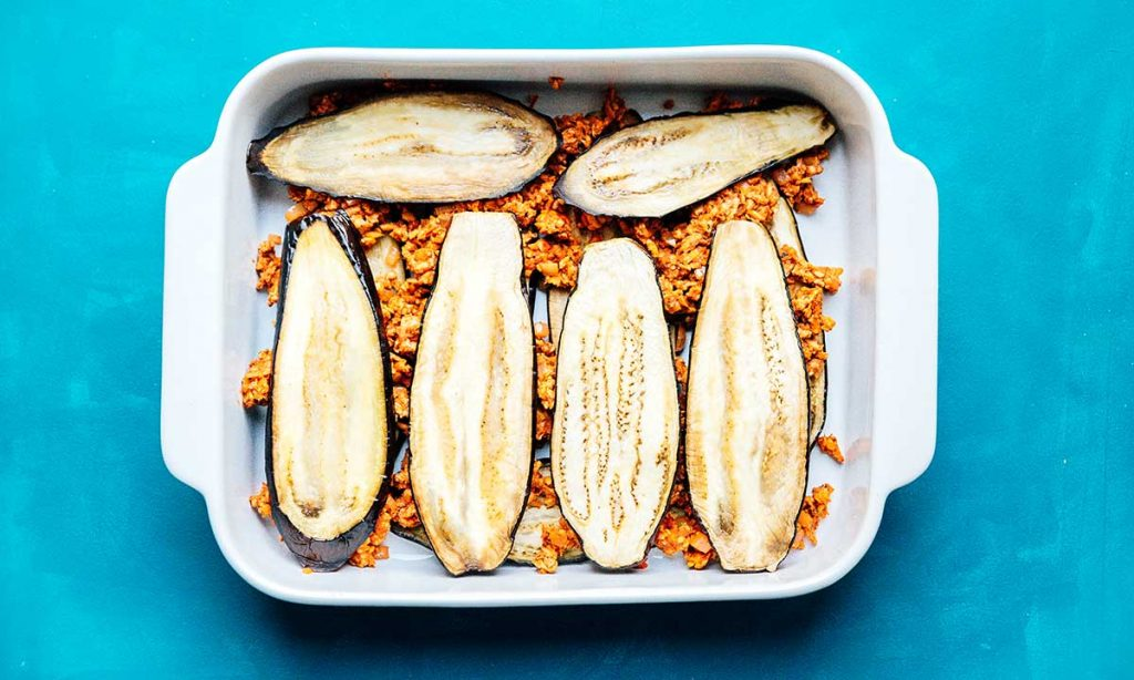 Casserole dish filled with layers of tempeh and eggplant