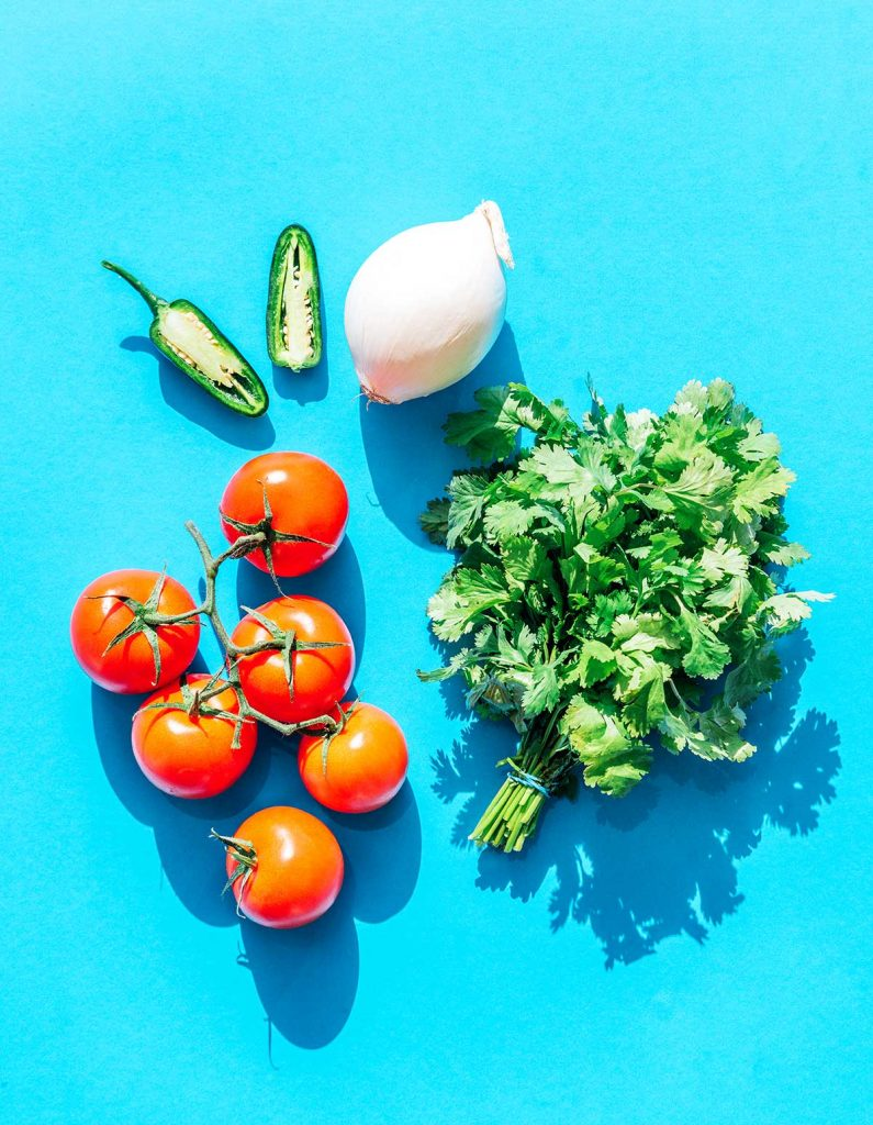Jalapeños, white onion, tomatoes, and cilantro laid out on a blue background