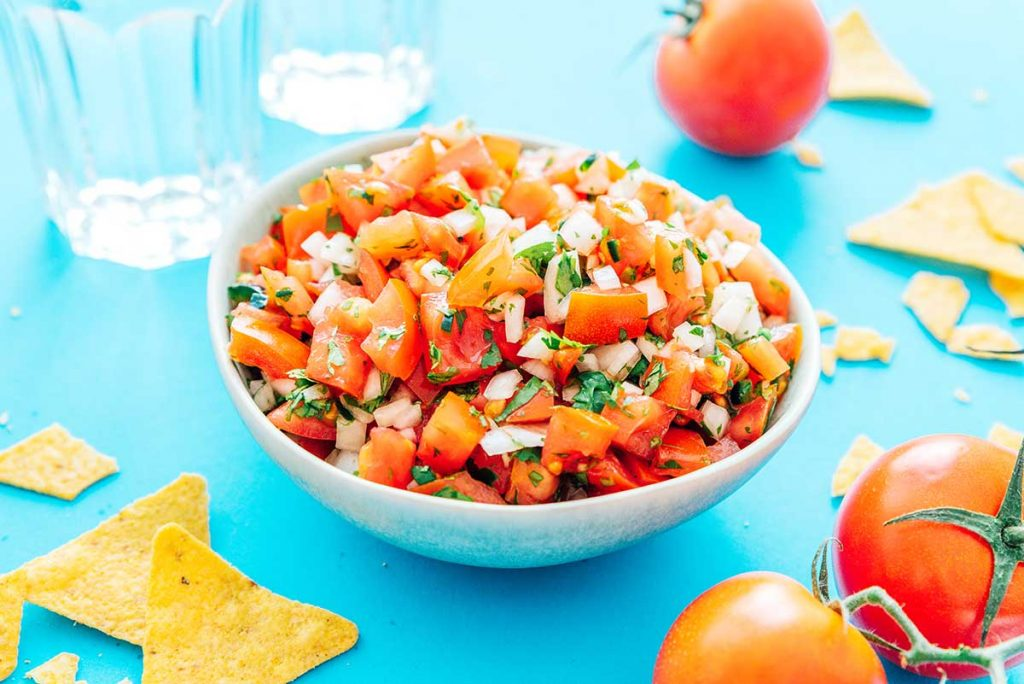 Pico de gallo in a white bowl with chips and tomatoes scattered around