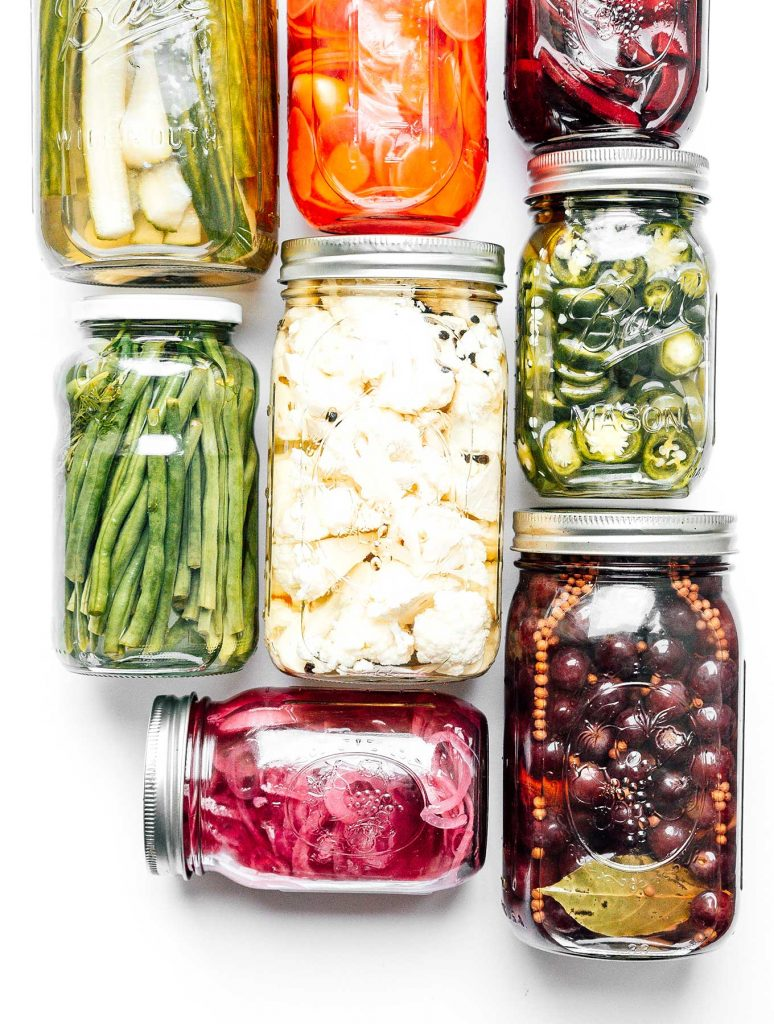 Pickled vegetables in mason jars on a white background