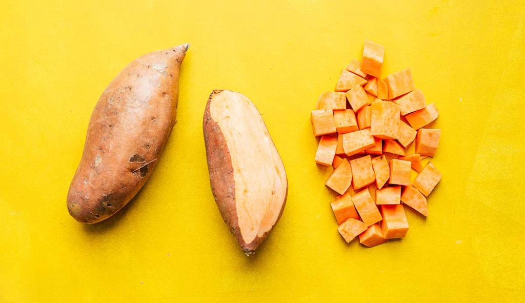 Two sweet potatoes and some cubed sweet potato pieces laid out in a row on a yellow background