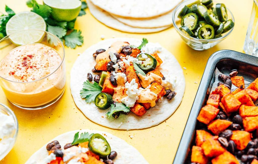 A sweet potato taco laid flat on a yellow background surrounded by various taco ingredients