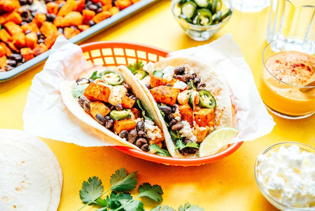 Two sweet potato tacos in a red basket surrounded by various taco ingredients