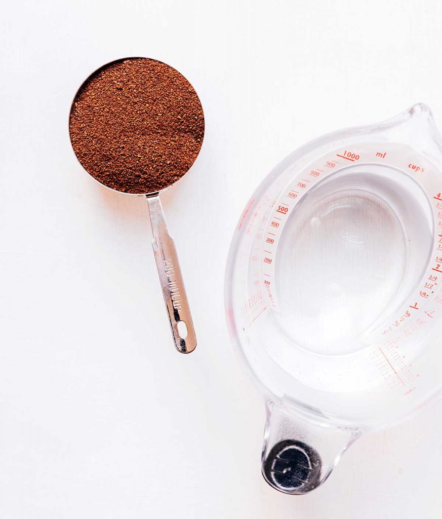 A measuring cup filled with coffee grounds and a second measuring cup filled with water